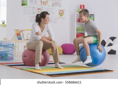 Physiotherapist and happy boy sitting on gym ball