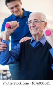 Physiotherapist Helping Senior Man To Lift Hand Weights