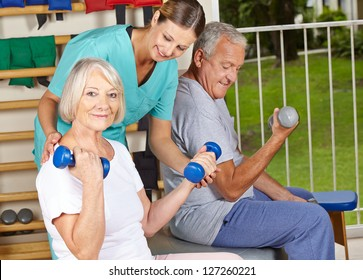 Physiotherapist helping senior people with dumbbell exercises