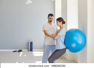 Physiotherapist helping young woman do wall squats with fit ball to get rid of backache and regain spinal health. Young female patient doing back exercise using fitball in physio room of modern clinic
