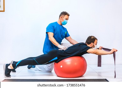 Physiotherapist with mask and a patient doing exercises with a rubber on a giant ball. Physiotherapy with protective measures for the Coronavirus pandemic, COVID-19. Osteopathy, sports chiromassage
