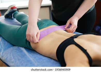 The physiotherapist massages the injured lower back of the athlete lying on the massage table with a kinesio tape. Masseur's hands holding the kinesio tape