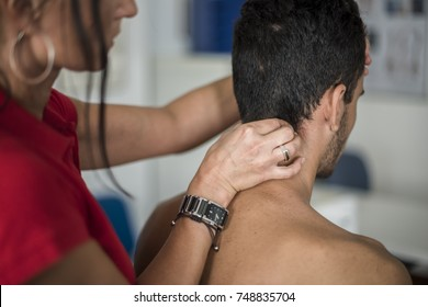 physiotherapist massages young patient to cure a cervical pain