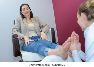 physiotherapist massaging female foot