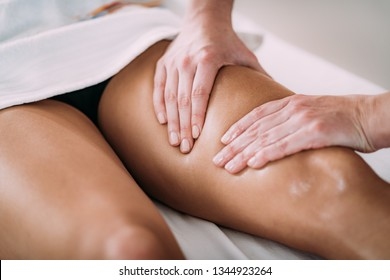 Physiotherapist massaging female patient with injured leg. Sports injury treatment.