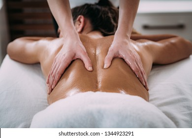 Physiotherapist massaging female patient with injured lower back muscle. Sports injury treatment.