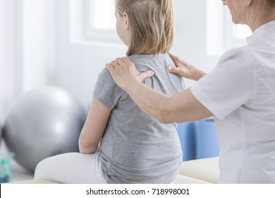 Physiotherapist massaging a girl with spine deformity during session in rehabilitation room