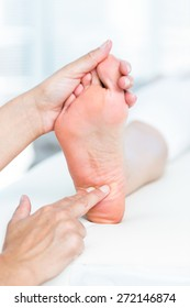 Physiotherapist massaging her patients foot in medical office