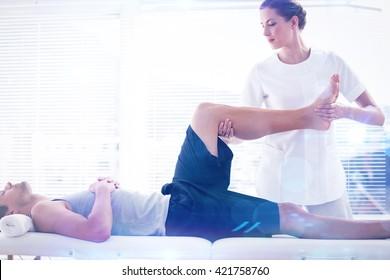 Physiotherapist massaging leg of man against lens flare