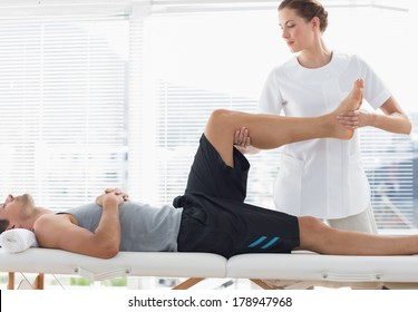Physiotherapist massaging leg of young man at spa