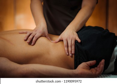 Physiotherapist massaging male patient with injured lower back muscle. Sports injury treatment.