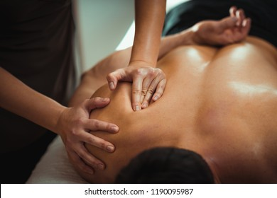 Physiotherapist massaging male patient with injured shoulder blade muscle. Sports injury treatment.