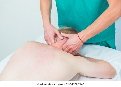 Physiotherapist massaging male patient with injured neck muscle. Sports injury treatment, reabilitation. Neurological physical examination. Osteopathy, chiropractic, physiotherapy