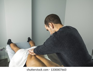 Physiotherapist massaging a young man back in a clinic. Physiotherapy concept