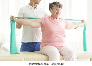 Physiotherapist providing help with easing the pain of joints through pnf exercises involving a scarf for his elderly patient