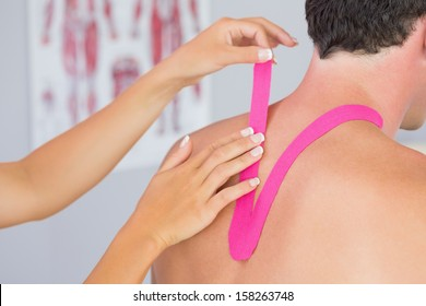 Physiotherapist putting on pink kinesio tape on male patients neck in bright office