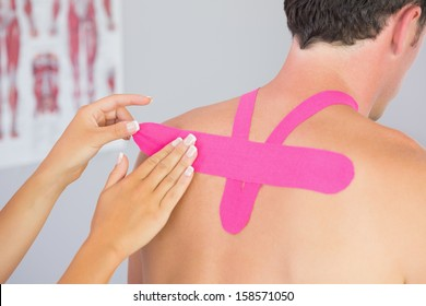 Physiotherapist putting on pink kinesio tape on male patients back in bright office