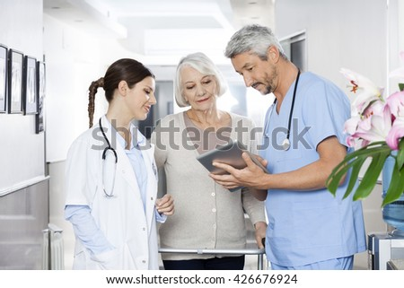 Physiotherapist Showing Reports To Patient And Doctor On Digital