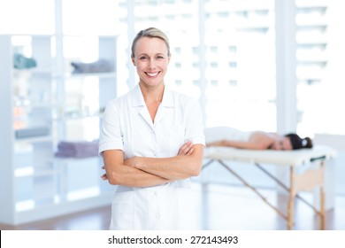 Physiotherapist smiling at camera arms crossed in medical office