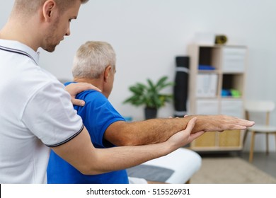 Physiotherapist treating a man for a elbow injury flexing the joint in his surgery or clinic, close up view of his hands