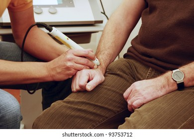 Physiotherapist treats patient with rsi on wrist with laser