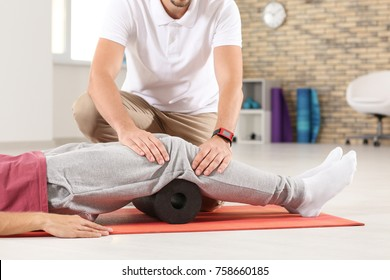 Physiotherapist working with young male patient in clinic