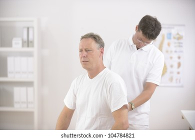 Physiotherapy: Physiotherapist examining senior man at office