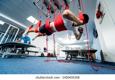 Physiotherapy. Suspension training therapy. Young man doing fitness traction therapy with suspension-based exercise training system. Treatment of pain in the spine.