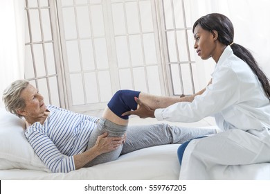 Physiotherapy - therapist doing leg stretching exercises with senior  patient