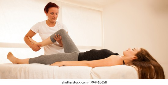 physiotherapy -therapist exercising with patient , working on leg stretching