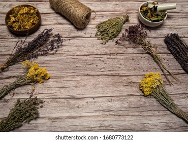Phytotherapy. Composition of dry herbs for herbal medicine. Collection, a mixture of various dried herbs in bundles and cups on a wooden background. Free space.