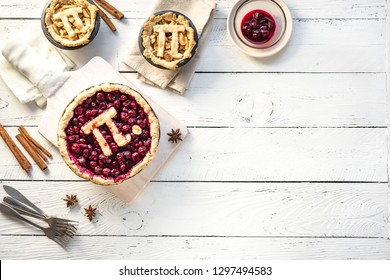 Pi Day Cherry and Apple Pies - homemade traditional various Pies with Pi sign for March 14th holiday, on white wooden background, top view, copy space.