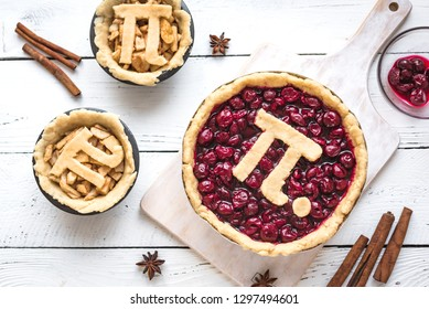 Pi Day Cherry and Apple Pies - making homemade traditional various Pies with Pi sign for March 14th holiday, on white wooden background, top view.