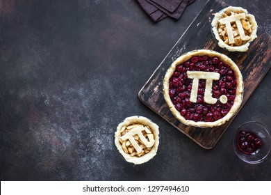 Pi Day Cherry and Apple Pies - making homemade traditional various Pies with Pi sign for March 14th holiday, on rustic background, top view, copy space.