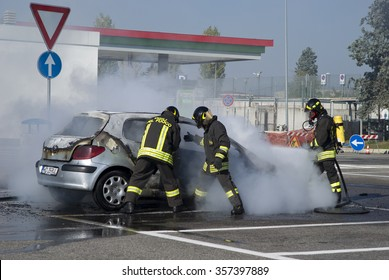 PIACENZA, ITALY - NOVEMBER 1, 2015: Italian firefighters extinguishing car on fire parked in a gas station, Piacenza, Northern Italy