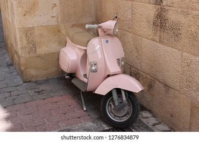 Piaggio Vespa scooter leaning on a stone wall on a street in Caravaca de la Cruz, Murcia, Spain. May 1st 2015