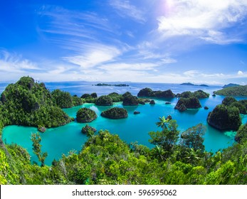 Pianemo ;a cluster of small coral islands surrounded by clear water and its hills covered by green vegetation ; Raja Ampat , Indonesia