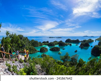 Pianemo ;acluster of small coral islands surrounded by clear water and its hills covered by green vegetation ; Raja Ampat , Indonesia