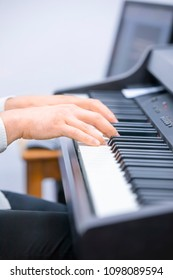 A pianist hand on piano keyborad. A pianist is playing a song at the church.