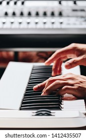 pianist hands playing white piano in recording studio