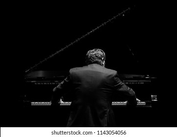 pianist from his back playing in the dark