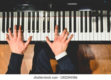 Pianist performing a piece on a grand piano with white and black keys., Seen from above...