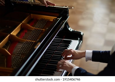 Pianist playing music on an old piano with an female transverse flute musician