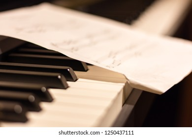Piano close-up with a page of musical notes.