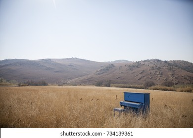 Piano in field with mountains
