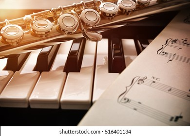 Piano and flute with golden shine and sheet music. Horizontal Composition.Front view - Shutterstock ID 516401134