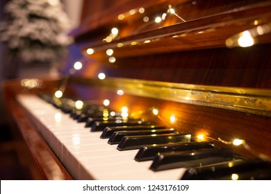 Piano keyboard illuminated with christmas lights. Romantic music background