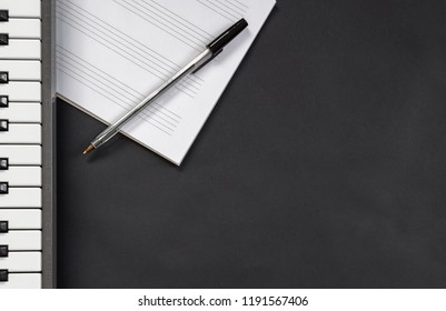 Piano or keyboard, music notebook in blank with pentagram and pen on black background with copy space. Concept of composing music, inspiration...