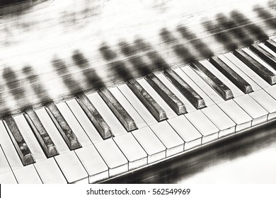 Piano keys with mirroring and copy space textured in black and white tones for a vintage style as background.