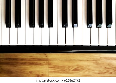 Piano keys on wood blurry background for copy space, high contrast
